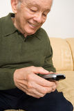 Elderly man with remote control Royalty Free Stock Images