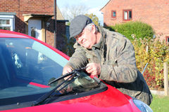 Elderly man renewing car wiper blades. An elderly man changing the windscreen wiper blades of a car Royalty Free Stock Images