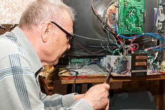 An elderly man repairing an old TV. In the room Royalty Free Stock Images
