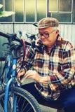 Elderly man repairs bicycles Stock Images