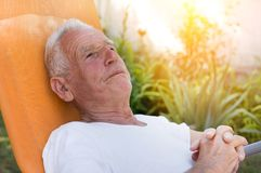 Elderly man resting in garden stock images
