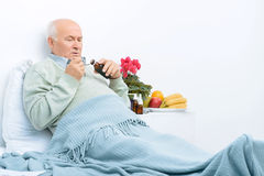 Elderly man rests in bed and pours cough syrup Royalty Free Stock Photography