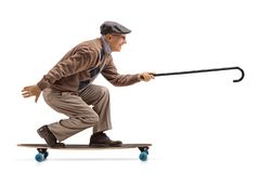 Elderly man riding a longboard and holding a cane. Isolated on white background royalty free stock images