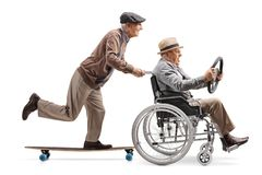 Elderly man riding a longboard and pushing a man holding a steering wheel and sitting in a wheelchair. Full length profile shot of an elderly men riding a royalty free stock photo