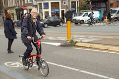 An elderly man riding an off-road sport bicycle. Amsterdam, Netherlands. An elderly man riding on an off-road sport bicycle. Bridge Blauwbrug, Amsterdam, the Stock Photography
