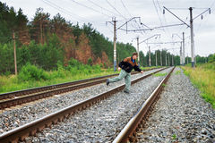 Elderly man crosses a railway embankment Royalty Free Stock Image