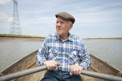 Elderly Man Rowing Boat. Senior men rowing a boat on a reservoir royalty free stock images