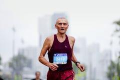 Elderly man runner running on city streets. Ekaterinburg, Russia - August 6, 2017: elderly man runner running on city streets in Europe-Asia Marathon Royalty Free Stock Photography