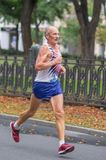 Elderly man running on a city street during 21 km distance of ATB Dnipro Marathon Stock Photo