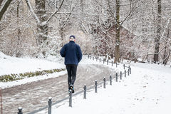 Elderly man is running in the snow in the park Royalty Free Stock Photos
