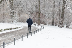Elderly man is running in the snow in the park Royalty Free Stock Photo