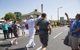 Elderly man running with torch. Olympic torch relay Royalty Free Stock Photos