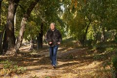 An elderly man runs along the path in the forest. An elderly man runs along the path in the autumn forest Royalty Free Stock Photo