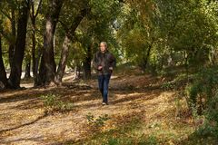An elderly man runs along the path in the forest. An elderly man runs along the path in the autumn forest Royalty Free Stock Image