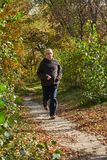 An elderly man runs along the path in the forest. An elderly man runs along the path in the autumn forest Stock Photography