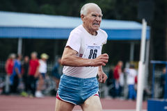 Elderly man runs 400 meters. Chelyabinsk, Russia - August 28, 2015:  elderly man runs 400 meters during championship of Russia on track and field athletics among Royalty Free Stock Photography