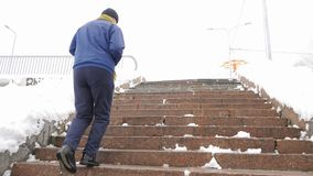 Elderly man runs up the stone stairs in winter. sports, cardio. Healthy life concept. 60 fps. 4k stock video
