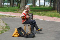 An elderly man in the Russian national costume playing the accordion in Suzdal, Russia. Royalty Free Stock Photography