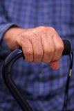 Elderly man's hand on cane Royalty Free Stock Photos