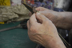 An Elderly Man`s Hands Craft Respect. Close up of elderly man`s expert hands as he works on an intricate project Royalty Free Stock Photo