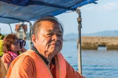 Elderly man sailing on river by long tail boat. Asian elderly men sailing on Songkaria river by long tail boat with sun light in evening time when vacation royalty free stock images