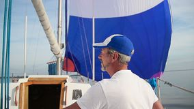 Elderly man sailor on sailboat, yachting, vacation, traveling. Stock footage stock footage