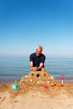 Elderly man with sand castle. Elderly man is building a sand castle at the beach with plastic toys royalty free stock images