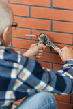 Elderly man screwed key tap. Outside Stock Image