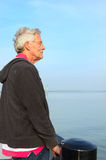 Elderly man at the sea. Elderly man is looking over the water of the sea royalty free stock image