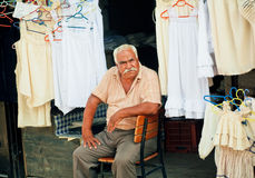 Elderly man sells lingerie and clothes on street market of old turkish village Stock Photos