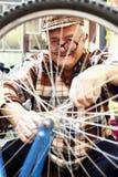 Elderly man serviced bikes Royalty Free Stock Photos