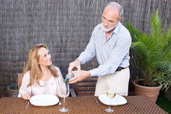 Elderly man is serving wine to a women. Elderly couple in garden drinking wine Royalty Free Stock Photo