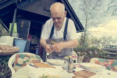 Elderly man setting a table outside. Royalty Free Stock Images
