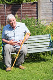 Elderly man with severe stomach pain. An elderly man sitting on a bench clutching his stomach with severe and sudden pain Royalty Free Stock Image