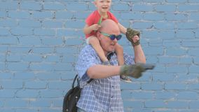 Elderly man with shaved head wearing sunglasses is holding small child and gun in his hands. Boy is holding child`s shovel. man shoots around at enemies stock video footage