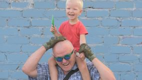 Elderly man with shaved head wearing sunglasses is holding small child and gun in his hands. Boy is holding child`s shovel. man shoots around at enemies stock footage