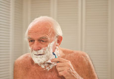 Elderly man shaving in front of a mirror Royalty Free Stock Photo