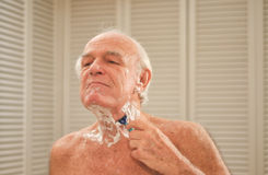 Elderly man shaving in front of a mirror Royalty Free Stock Photos