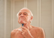 Elderly man shaving in front of a mirror Royalty Free Stock Image