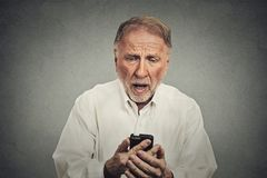 Elderly man, shocked surprised by what he sees on his cell phone Royalty Free Stock Photo