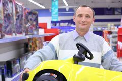 Elderly man in shop with children's car Royalty Free Stock Photography
