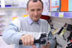 Elderly man in shop with drill Stock Photography
