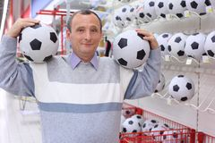 Elderly man in shop with footballs Stock Photography