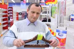 Elderly man in shop with hanger Stock Images