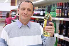 Elderly man in shop holds wine bottle Stock Photos