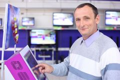 Elderly man in shop at information screen. Smiling elderly man in shop at information screen royalty free stock images