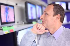 Elderly man in shop looks at TV. Elderly man in modern shop looks at TV royalty free stock photo
