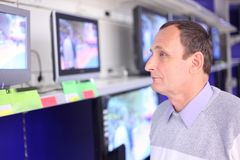 Elderly man in shop looks at TVs. Elderly man in modern shop looks at TVs royalty free stock photography