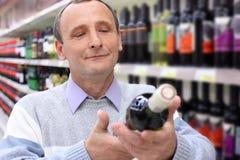 Elderly man in shop looks on wine bottle Royalty Free Stock Image