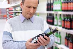 Elderly man in shop looks on wine bottle Royalty Free Stock Photography